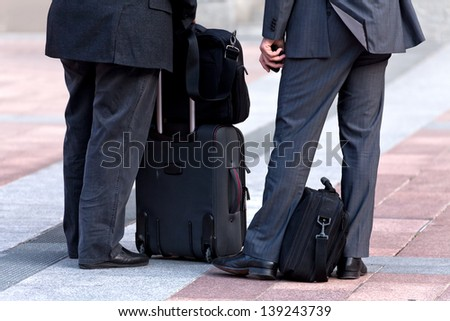Two businessman with a business luggage. Urban scene.