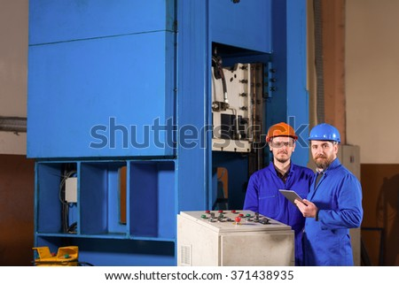 Two businessman working in factory. - stock photo