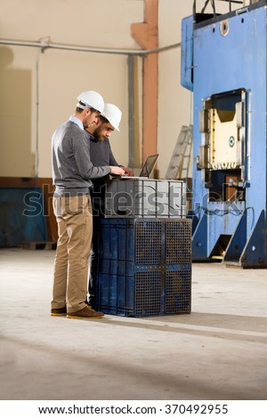 Two businessman working with laptop in factory. - stock photo
