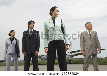 Two businessmen and two businesswomen standing at an airport - stock photo