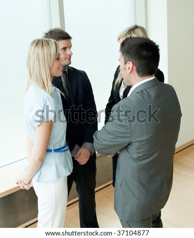 Two businessmen and two businesswomen talking in an office
