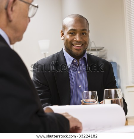 Two businessmen are in a meeting at an office.  The younger man is smiling at the camera.  Square framed shot. - stock photo