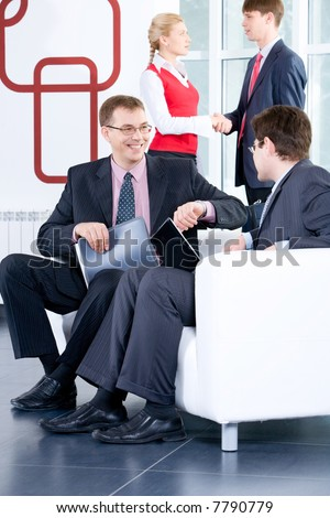 Two businessmen are negotiating on the background of people shaking each other's hands - stock photo