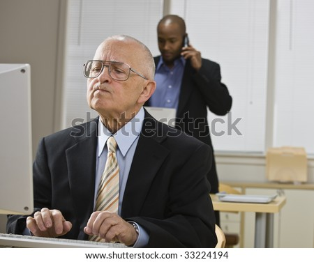 Two businessmen are working in an office.  The older man is working on a computer and the younger man is talking on a cell phone.  Horizontally framed shot. - stock photo