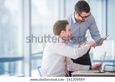 Two businessmen at work with a tablet in office - stock photo