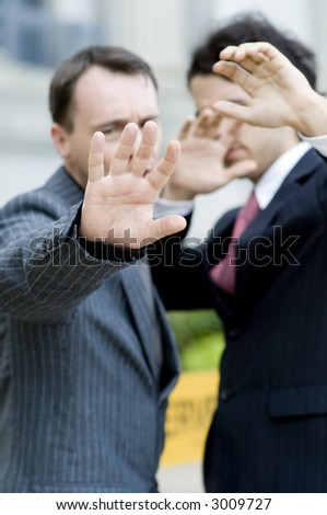 Two businessmen avoiding the camera (focus on hand)