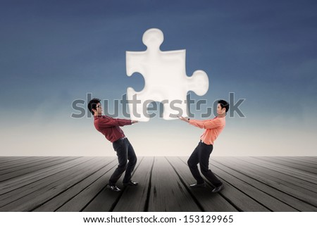 Two businessmen bring a puzzle together over blue sky background - stock photo