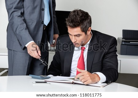 Two businessmen calculating finances at desk in office - stock photo