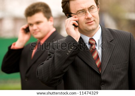 Two businessmen calling by mobile over blurred house on background