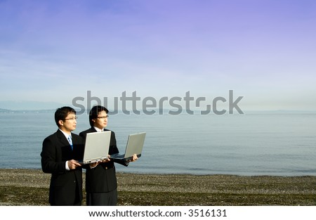 Two businessmen carrying their laptops at the beach - stock photo
