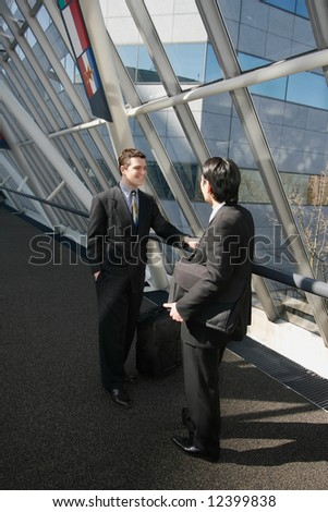 Two businessmen chatting in the lobby of an office building - stock photo