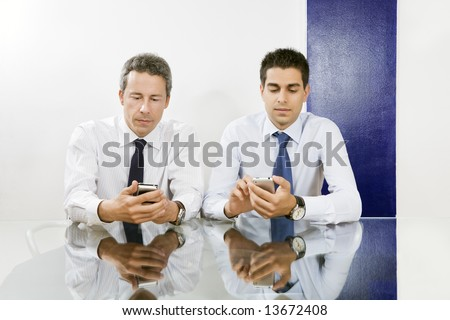 Two businessmen checking blackberries in meeting room. - stock photo