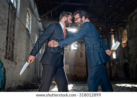 Two businessmen closing a deal and hiding knives - stock photo