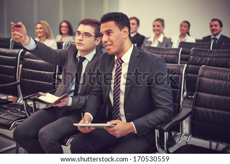Two businessmen communicating at seminar on background of their colleagues