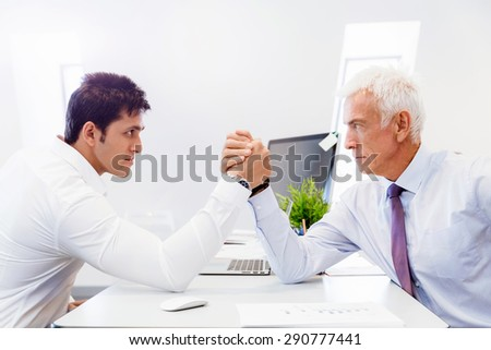 Two businessmen competing arm wrestling in office - stock photo
