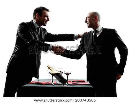two businessmen dinning handshaking in silhouettes on white background - stock photo