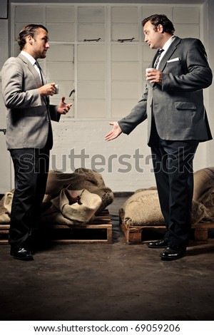 two businessmen discuss the coffee and drink espresso together
