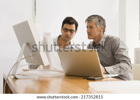 Two businessmen discussing a blueprint in an office - stock photo