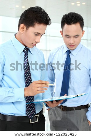 Two businessmen discussing a business chart growth