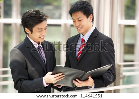 Two Businessmen Discussing Document Outside Office