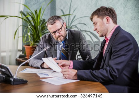 two businessmen discussing documents in the office - stock photo