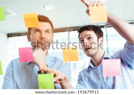 Two businessmen discussing ideas written on sticky notes - stock photo