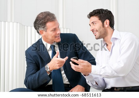 Two businessmen discussing together on a news on a smart phone - stock photo
