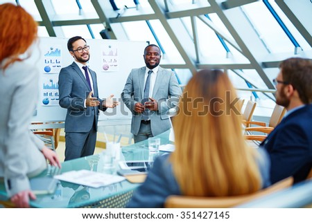 Two businessmen explaining colleagues latest data - stock photo