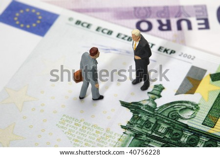 two businessmen figurines standing on euro banknotes, financial deal concept - stock photo