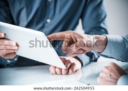 Two businessmen having a discussion over information displayed on a tablet computer, close up of their hands pointing to the screen in a teamwork concept - stock photo