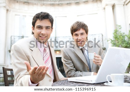 Two businessmen having a meeting in a classic coffee shop terrace, while one of them is using his hand to make gestures to the camera. - stock photo