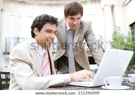 Two businessmen having a meeting while sitting in a classic coffee shop terrace, using a laptop computer and smiling. - stock photo
