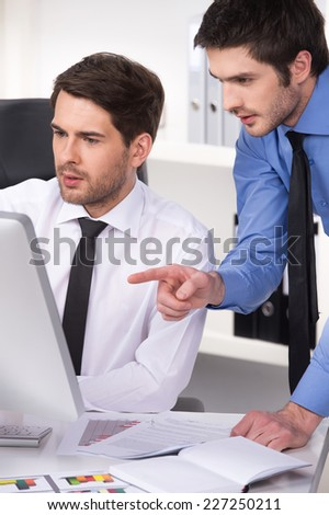 two businessmen having discussion in office. closeup on two businessmen looking at screen with graphs on table - stock photo