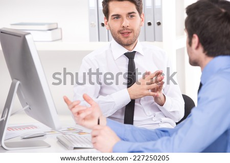 two businessmen having discussion in office. over shoulder view of businessmen looking at each other and using laptop - stock photo