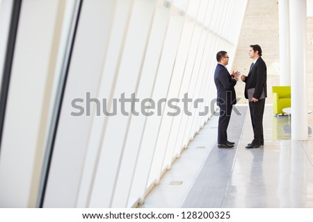 Two Businessmen Having Informal Meeting In Modern Office - stock photo