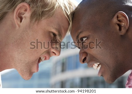 Two businessmen head to head having an argument in the city. - stock photo