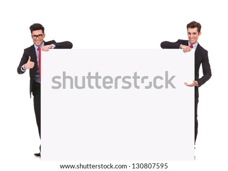 two businessmen holding a big blank sign , one presenting and one making the ok thumbs up gesture - stock photo