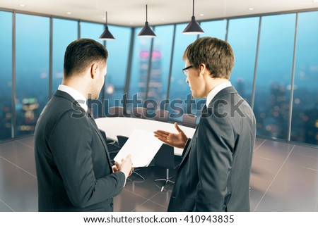 Two businessmen holding piece of paper and discussing something in conference room interior at night. 3D Rendering - stock photo