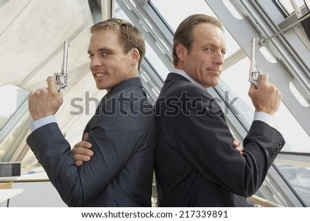 Two businessmen holding revolvers and standing back to back - stock photo