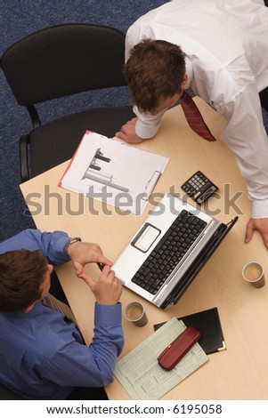 Two businessmen in a discussion, looking at laptop, paperwork; shot from above.