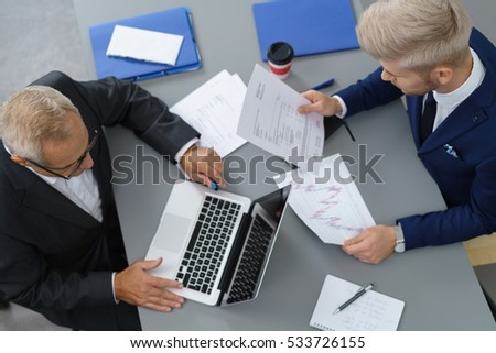 Two businessmen in a meeting seated at a table in the office analysing a set of performance graphs, overhead view