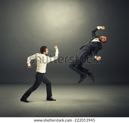 two businessmen in fight. one man standing and hitting, second man flying and screaming. photo in the dark room - stock photo