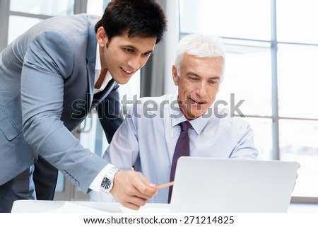 Two businessmen in fornt of computer in office - stock photo