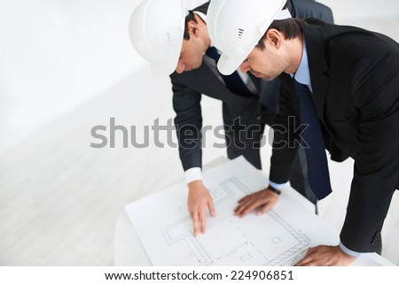 Two businessmen in helmets indoors - stock photo