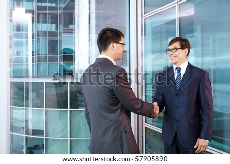Two businessmen in office shake hands - stock photo