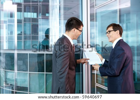 Two businessmen in office to discuss contract - stock photo