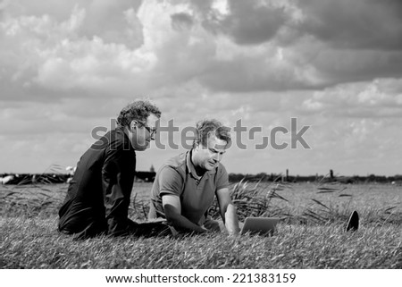 Two businessmen, informally dressed, working with a computer in a rural area, a typically Dutch landscape with beautiful clouds in the sky, using wireless broadband connection - stock photo
