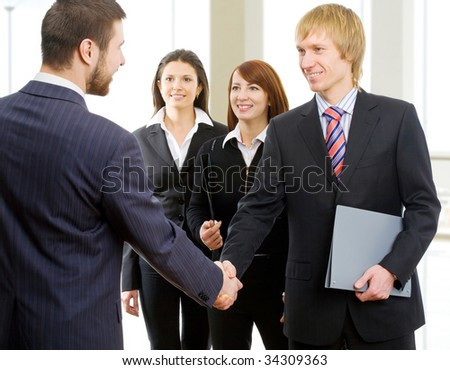 Two businessmen join their hands together - stock photo