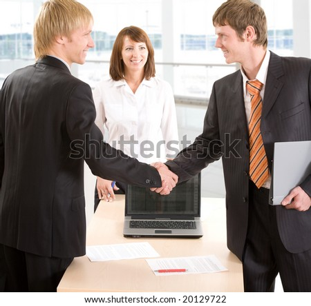 Two businessmen join their hands together next to a secretary - stock photo