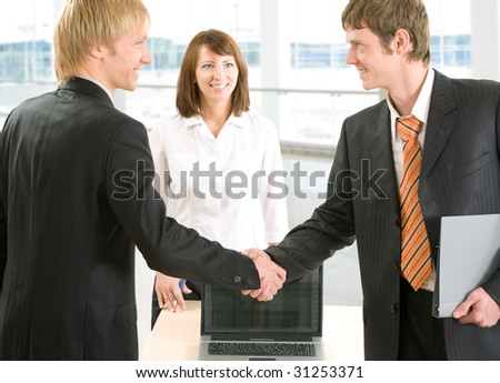 Two businessmen join their hands together next to a secretary
